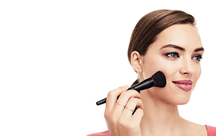 Woman with Mary Kay Powder Foundation Brush representing the variety of finishes and coverage options available in the Foundation Guide.